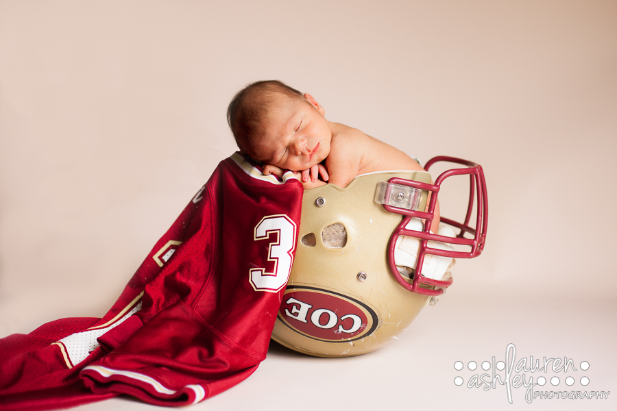 Newborn baby boy photographer in cedar rapids baby boy photo in a football helmet